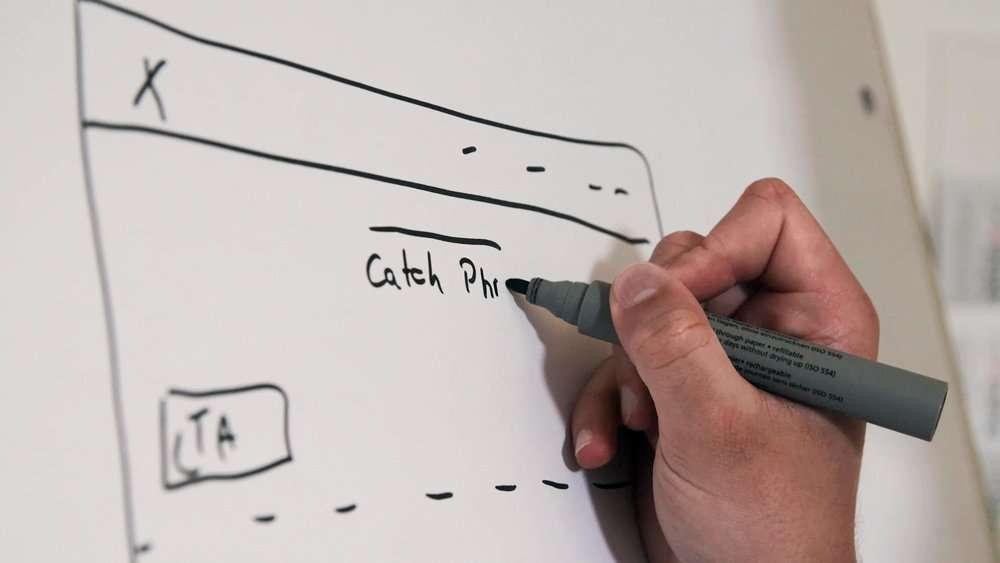 Eine Hand zeichnet ein Wireframe einer Webseite