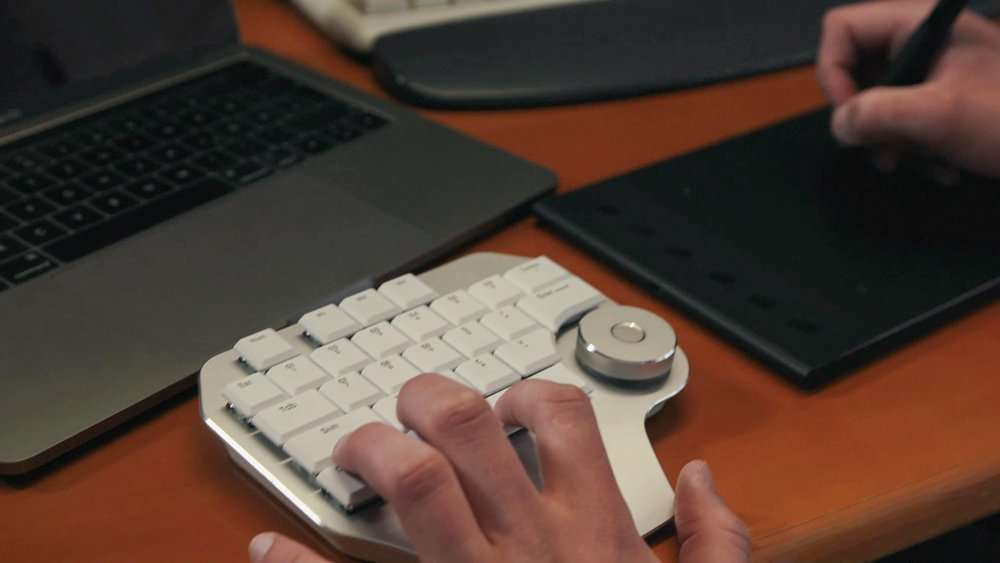 Eine Hand auf einer Design Tastaturund eine Hand mit einem Designstift in der Hand