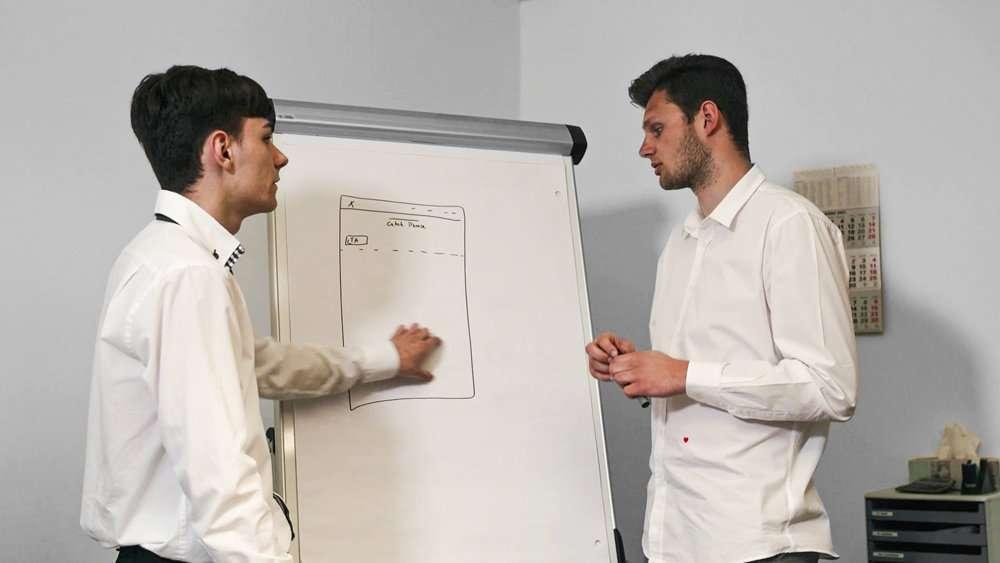 Zwei Männer die zusammen an einem Flipchart arbeiten