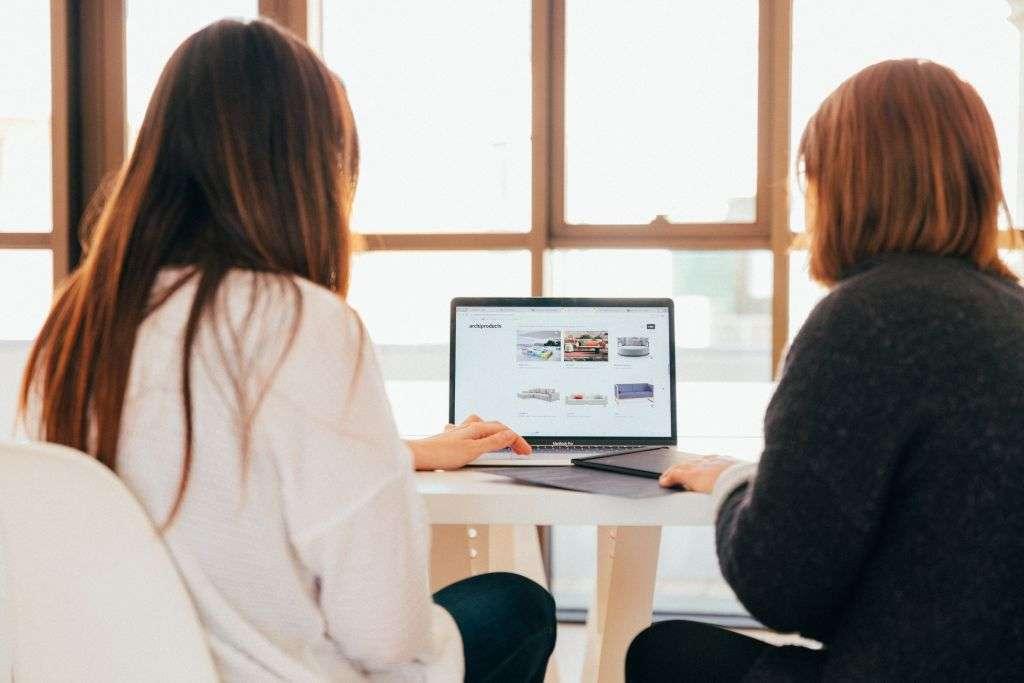 zwei Frauen, die gemeinsam an einem Laptop arbeiten