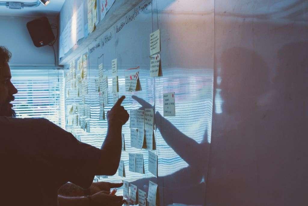 Ein Mann zeigt auf ein Whiteboard und plant eine wirksame Online-Strategie